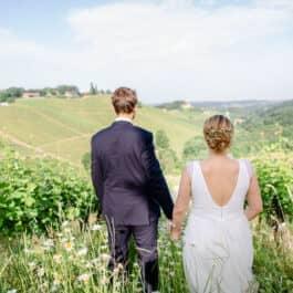 Edle Weingarten Trauung An alle Weinliebhaber: Traumhaft edle Location zum Ja-Sagen. Gibt es ein schöneres Plätzchen zum Heiraten als inmitten der südsteirischen Weinberge und der Sauvignon Blanc Rebstöcke? Wohl kaum! Mediterranes Klima verbunden mit herrschaftlichen Weinbergen soweit das Auge reicht, jeweils authentisch, im Süden der Steiermark. Hier kann ganz leicht Ihre Traum-Hochzeit in einer wunderbaren Location stattfinden. Neben der Pracht der Dahlien und der herbstlichen Verfärbung der Weingärten, bietet der Garten bei einer Hochzeit im Freien eine atemberaubende Kulisse. Vor allem in der Herbstzeit fungiert der Weinberg als wunderbares Fotomotiv für Sie und Ihre Liebsten. Weinberg Hochzeiten sind ein klassischer Hochzeitsort für jede Art von Paar, sie können leicht an Ihren persönlichen Stil angepasst werden. Gerade das lässt Paaren die Freiheit die Hochzeit ganz nach Ihren Wünschen und Ideen zu gestalten. Eine romantische Trauung, danach Fotoshooting zwischen den Weinstöcken – um hier ins Schwärmen zu geraten, muss man nicht einmal groß ein Wein Fan sein. Das Ambiente des Weingartens spricht für sich. Wollen auch Sie sich Ihr Ja-Wort bei einer herrlich schönen Trauung unter freiem Himmel vor der Kulisse des malerischen Weingartens geben? Wenden Sie sich gerne für eine Terminvereinbarung an mich!